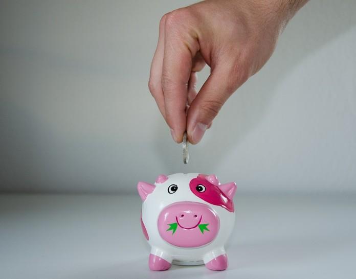 コインをぶたの貯金箱に入れる