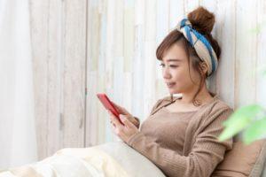 家のスマホで韓国ドラマを無料視聴する女性